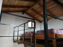 The second floor is built of wood and there are three single beds